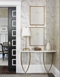 Custom framed intaglios hang above a console with gilded legs by Porto Romana.