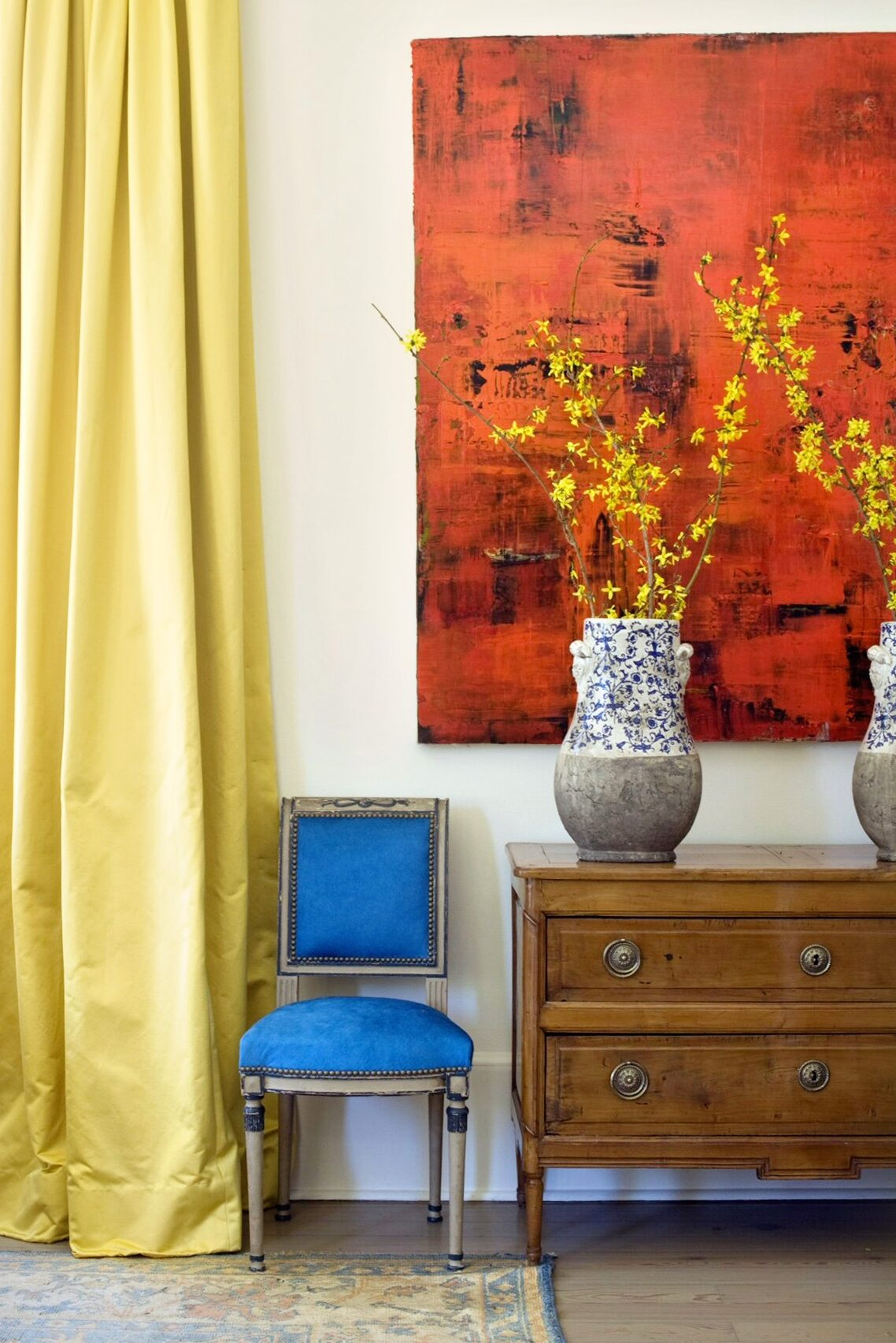 An overscaled bold red modern painting pops against Pierre Frey yellow satin curtains, cobalt blue velvet Louis XVI chairs and an antique chest.