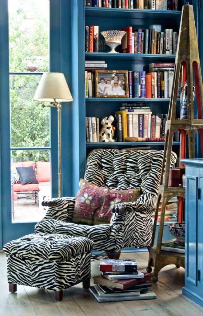 An étagère found by the client in a Magazine Street antique shop sits next to a mod zebra upholstered chair with vintage pillow.