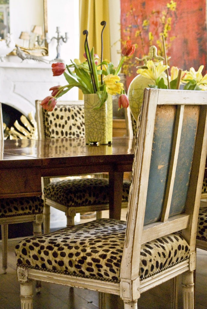 Worn antique blue leather on the backs of dining room chairs is revved up with leopard on the front.