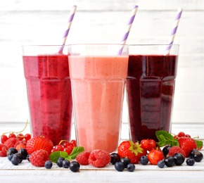 Three glasses of smoothies with different berries on wooden background